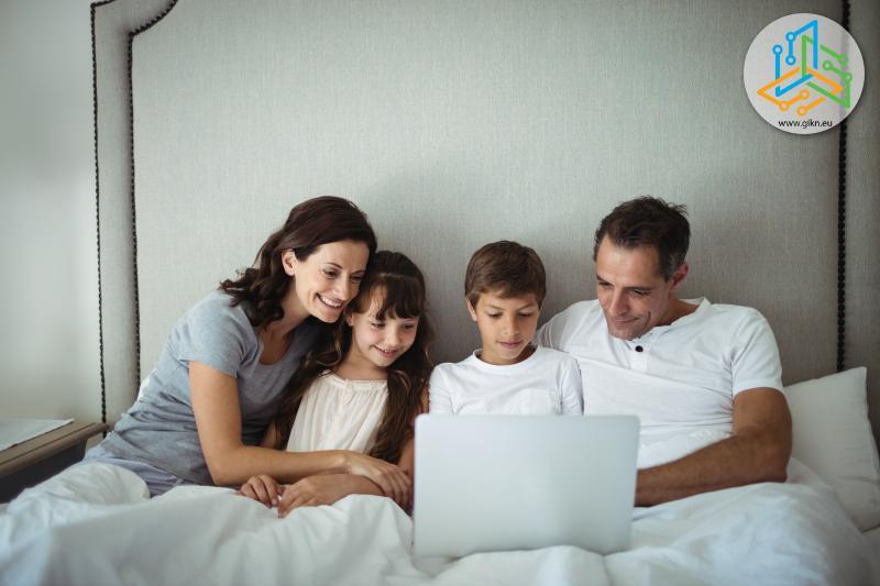 Семейство с лаптоп в спалнята